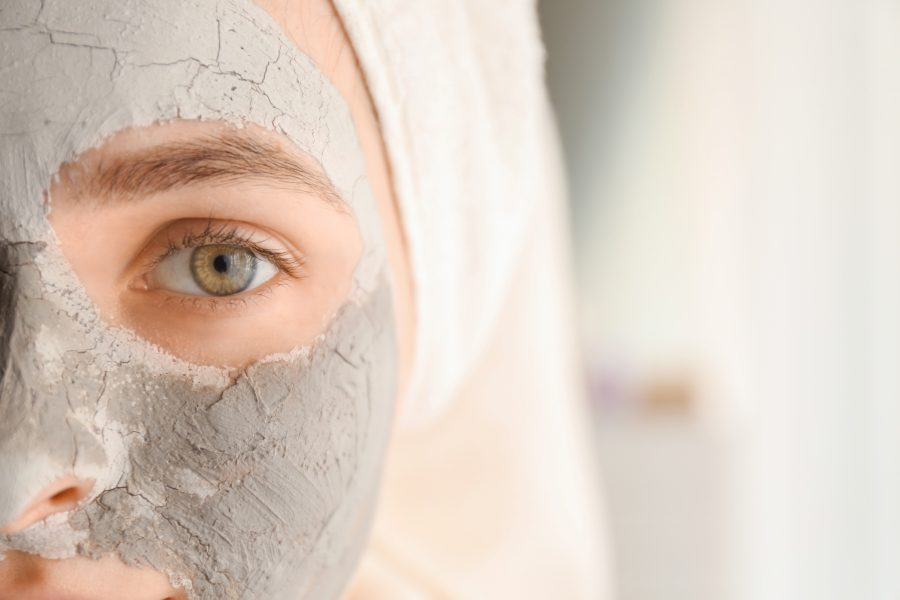Young woman with clay mask at home, closeup